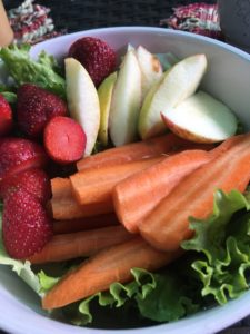 Raw fruit and veggie plate. Organic apples, carrots, strawberries on a bed of lettuce.