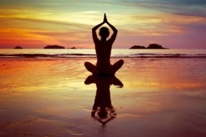 A woman on the beach at sunset practicing yoga, sitting in lotus pose.
