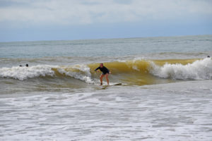 Me surfing in the green waves, standing up on my board and riding the wave in.